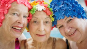3 senior women friends wearing swimming caps