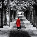 Solitary lady in red coat walking down a dark path