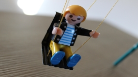 Toy with smile swinging on swing set.