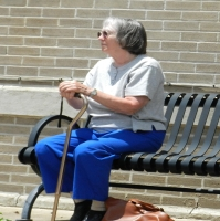 Older lady sitting alone on a bench with a cane.