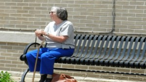 Older lady waiting on a bench alone and with a cane.