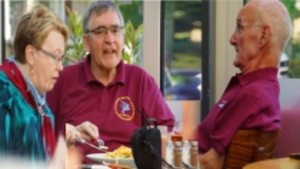 Three older adults enjoying mealtime