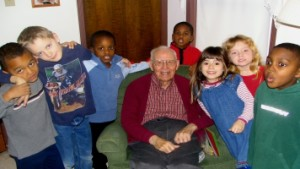 Children smiling with an older, male caregiver