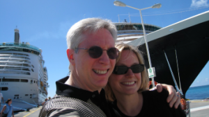 David Kramer and wife Tiffany in front of a cruise ship as he travels despite his Alzheimer's