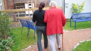 Daughter Walking Mom Around Memory Care