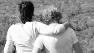 Daughter embracing mom who has dementia